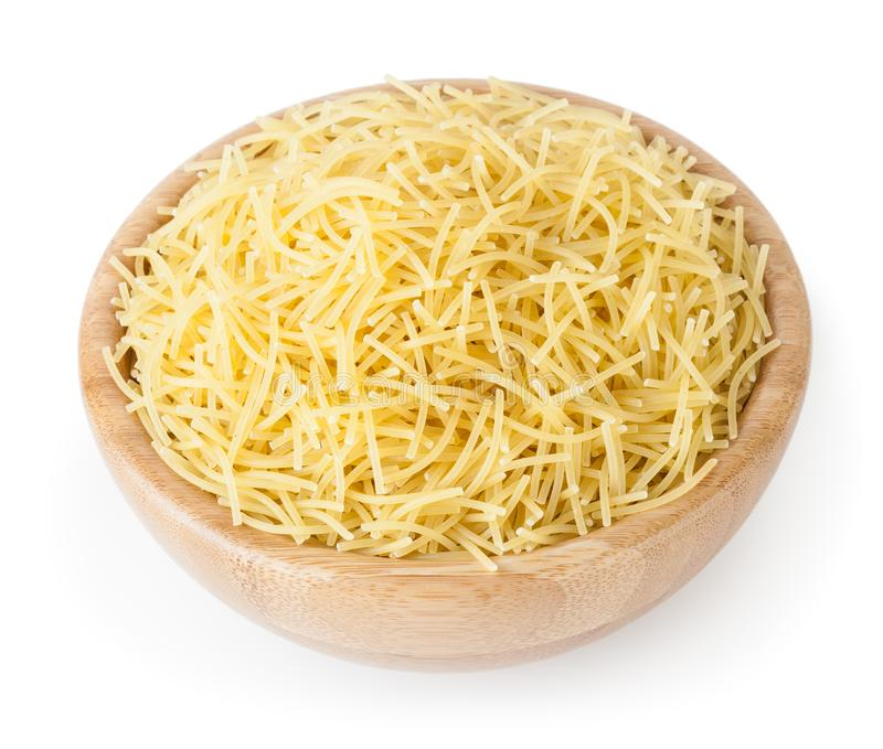 Uncooked vermicelli pasta in wooden bowl isolated on white background. With clipping path stock photo