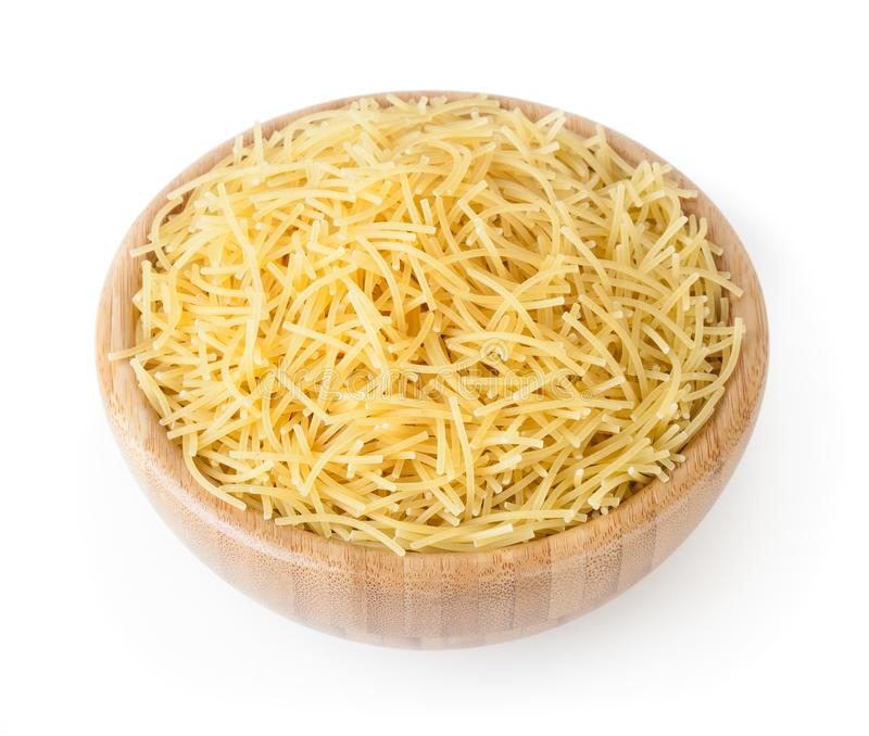 Uncooked vermicelli pasta in wooden bowl isolated on white background. With clipping path stock photography