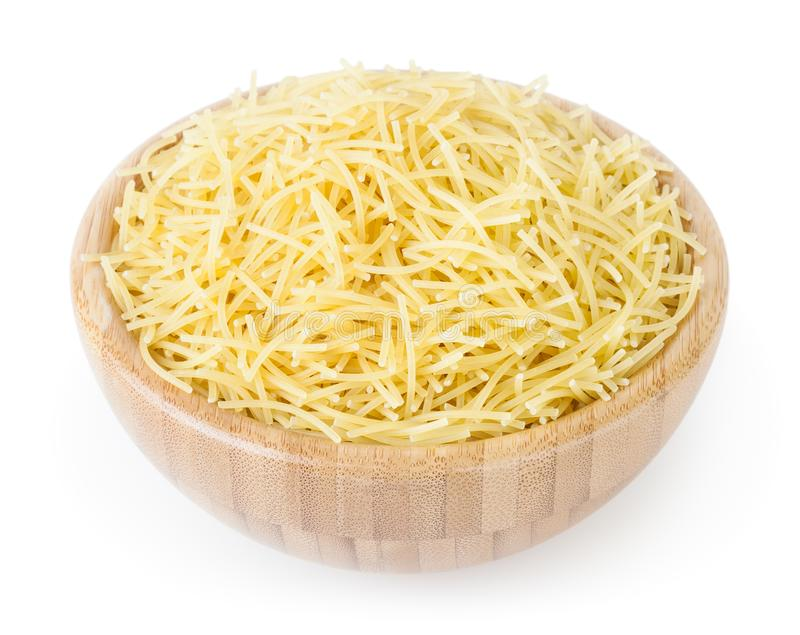 Uncooked vermicelli pasta in wooden bowl isolated on white. Background with clipping path royalty free stock image