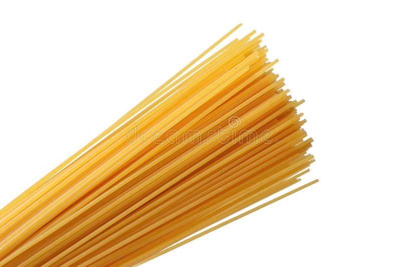 Uncooked yellow wheat spaghetti noodles on white background stock photos