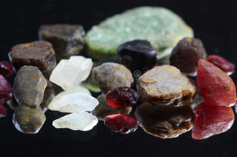 Uncut and raw gem crystals. Uncut and crude gem crystals. These natural rough gems are from Lemmenjoki national park in Finnish Lapland. Front row left to right royalty free stock photo