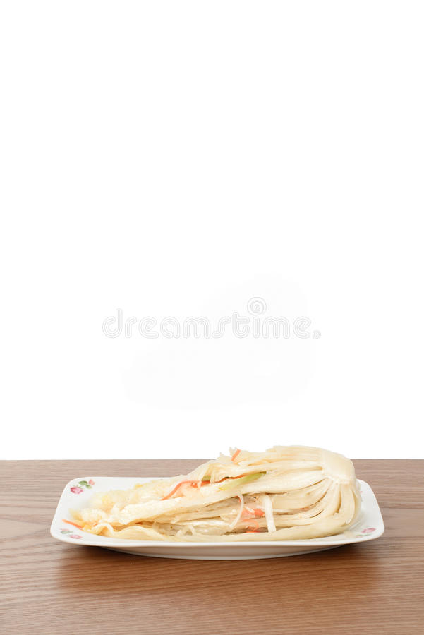 Uncut white Gimchi. Uncut Baek-Gimchi on a wooden plate, isolated on white royalty free stock image