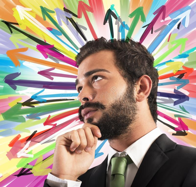Undecided businessman. Businessman thinks with background of colored arrows stock images