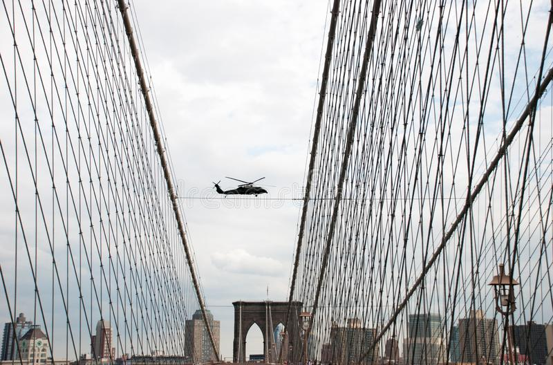Undefined helicopter flying over Brooklyn Bridge in New York City stock photography