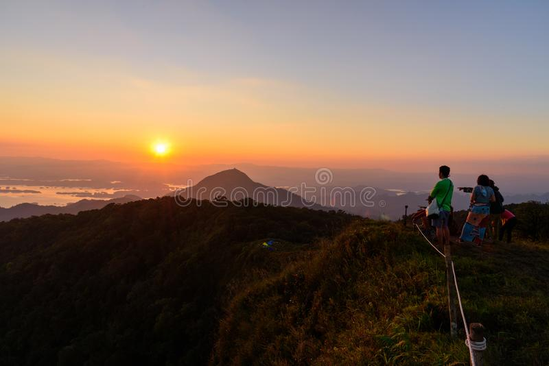 Undefined traveler standing on high mountain in sunset time. /sunset royalty free stock image