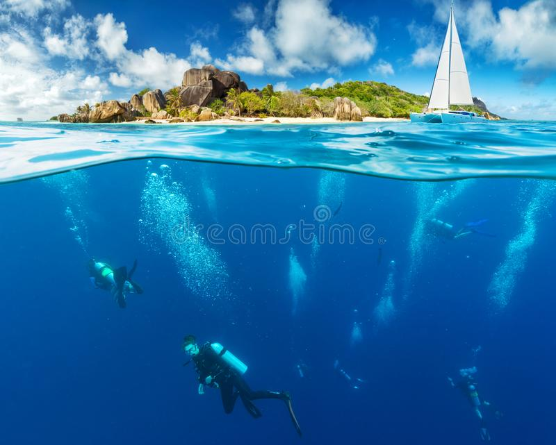 Under and above water surface view of divers royalty free stock photography