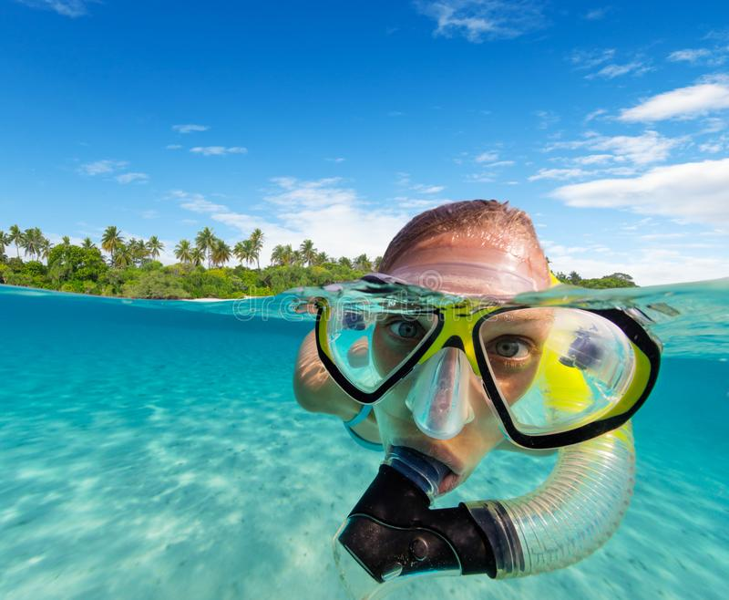 Under and above water view of woman snorkeling stock images