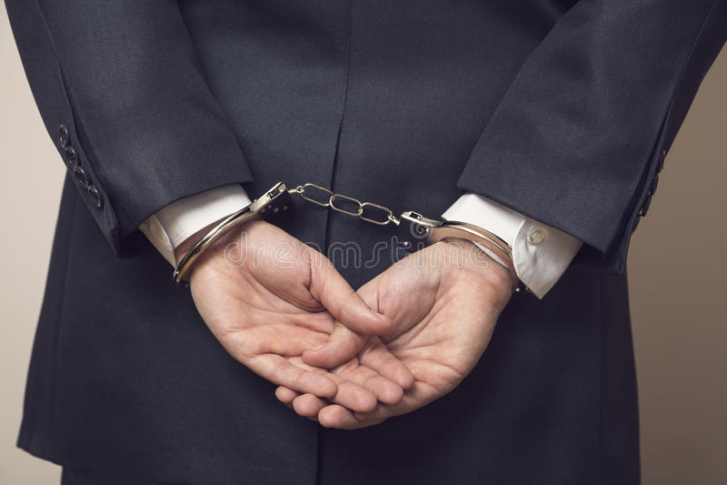 Under arrest. Business man in a suit with handcuffs, under arrest for corruption and bribery. Selective focus stock photography