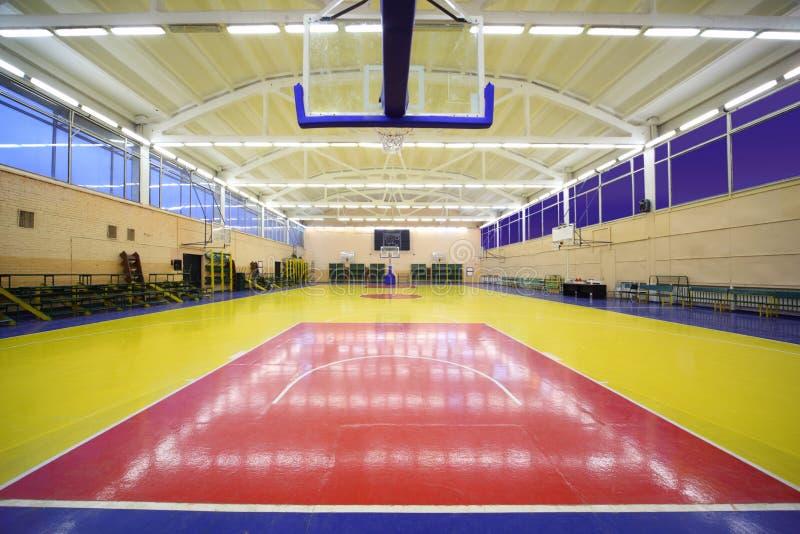 Under basket inside lighted school gym hall stock images