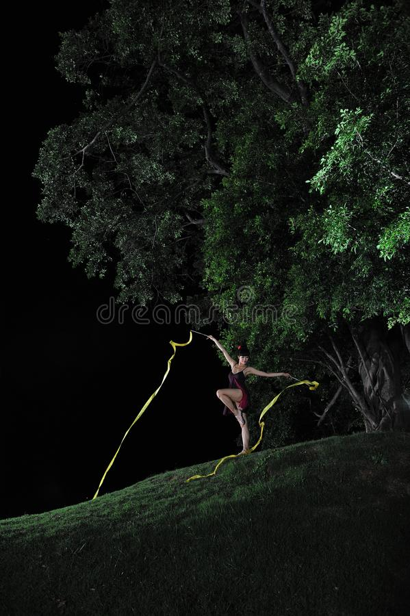 Asian girl dancing ballet under big tree at night. Under the big tree at night, Asian girls dancing ballet, charming night, open-air stage, close to nature stock images