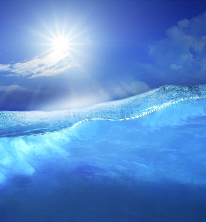 Under blått vatten för klart hav med solen som skiner på ovannämnt bruk för himmel för arkivbild