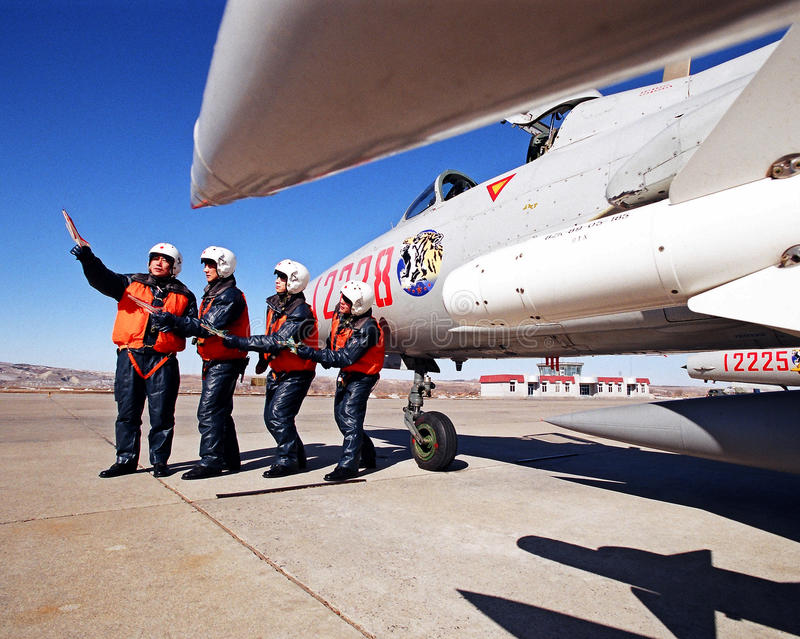Under the blue sky, a military airport, four pilot beside the fighters eight aircraft flight simulation training. The blue sky, pilots and aircraft stock photo