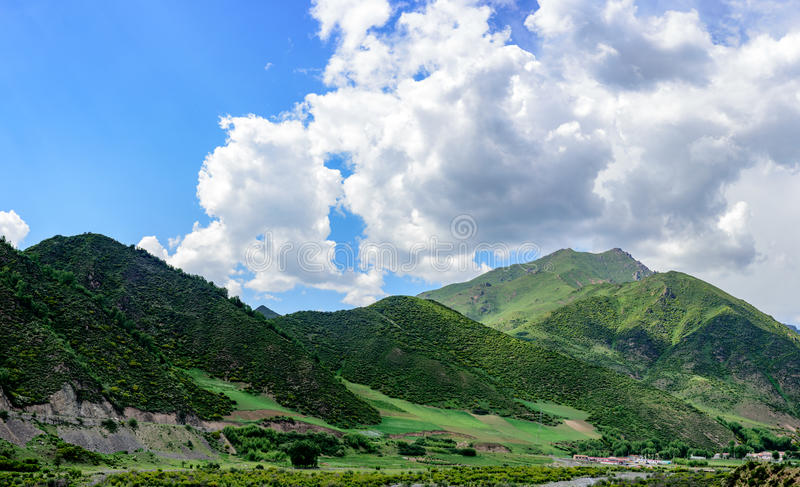 Under the clear weather, the blue sky, the white clouds, the green mountains make up the beautiful scenery royalty free stock photo