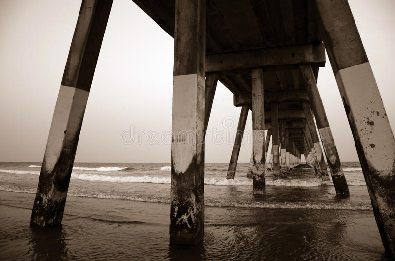 Under Concrete Beach Pier at Wrightsville Beach. Angled sepia perspective of Wrightsville Beach, North Carolina concrete pier disappearing into Atlantic Ocean stock image
