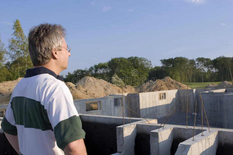 Under Construction. Man overlooking construction of new house royalty free stock photography