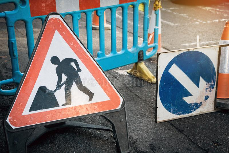 Under construction board sign on the closed road with arrow sign and traffic cone. Caution symbol under construction, work in. Progress sign royalty free stock image