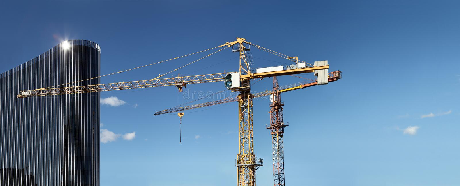 Under construction site building with crane and glass skyscraper royalty free stock photography
