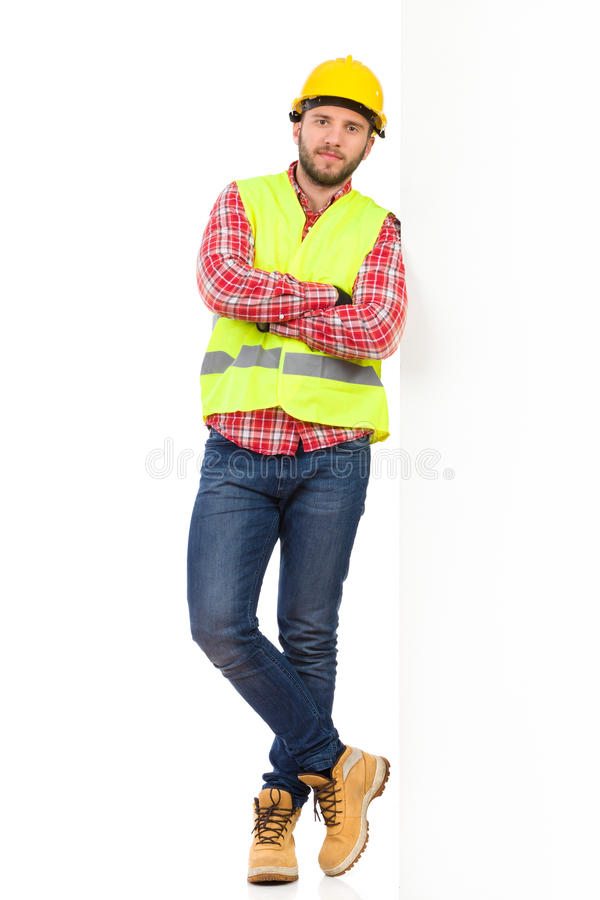 Under construction. Construction worker in yellow helmet and reflective lime waistcoat lean on a wall and holding arms crossed. Full length studio shot isolated royalty free stock images