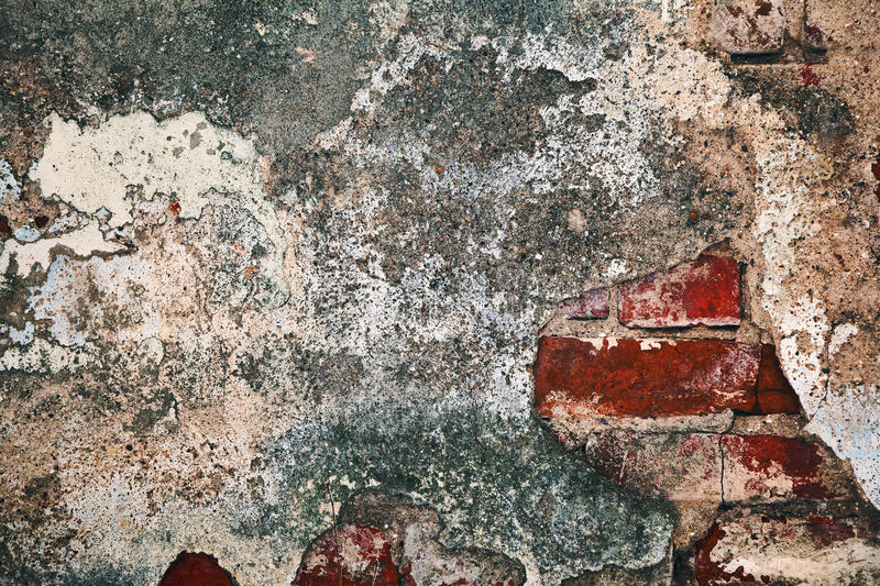 Under the crumbling plaster and cement visible brickwork. Decaying wall grunge texture. Under the crumbling plaster and cement visible brickwork royalty free stock photos