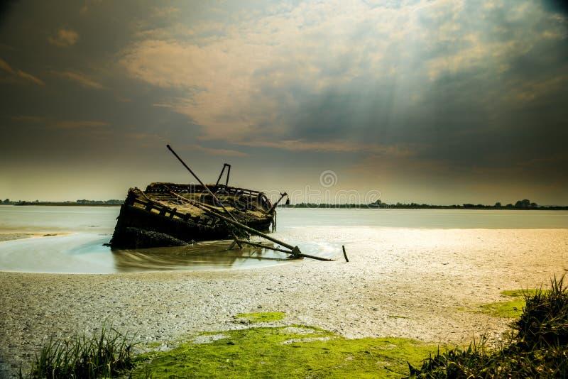 Under en illavarslande och dramatisk himmel håller denna ensamma skeppsbrott att räkna tidvattnen av floden arkivfoto