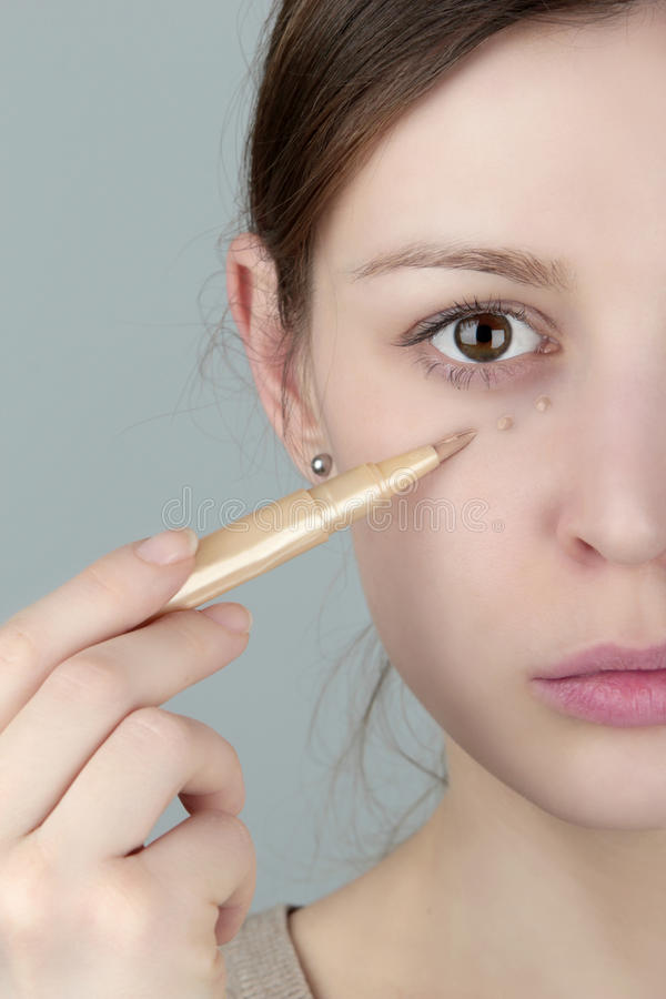 Under eye concealer. Young woman applying under eye concealer stock photography