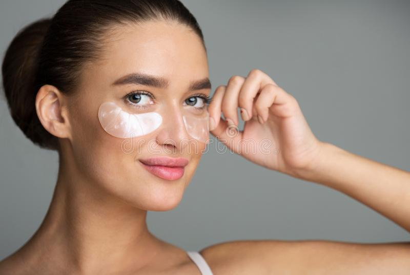 Under Eye Treatment. Woman With Patches, Grey Background stock image