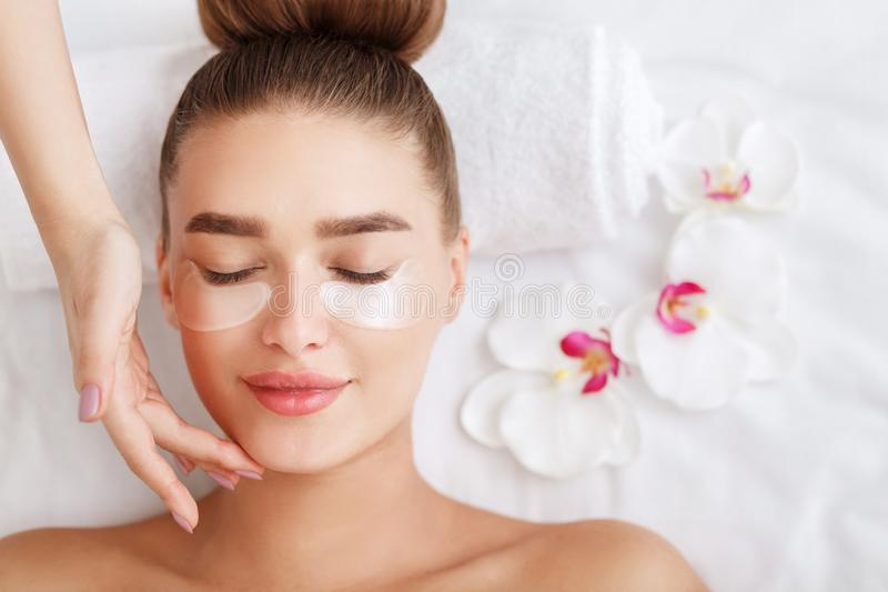 Under eye treatment. Woman with patches, relaxing in spa center stock image