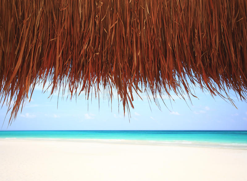 Under a thatched hut at a resort beach stock photos