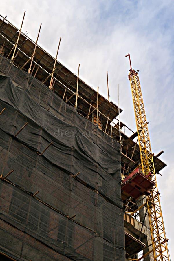 Under konstruktionsbyggnad med svart skyddande förtjäna omge en byggnad royaltyfri fotografi