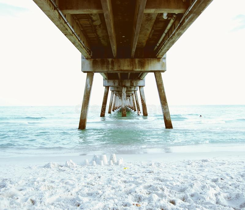 Under the Pier. View out to sea under a long pier royalty free stock photo