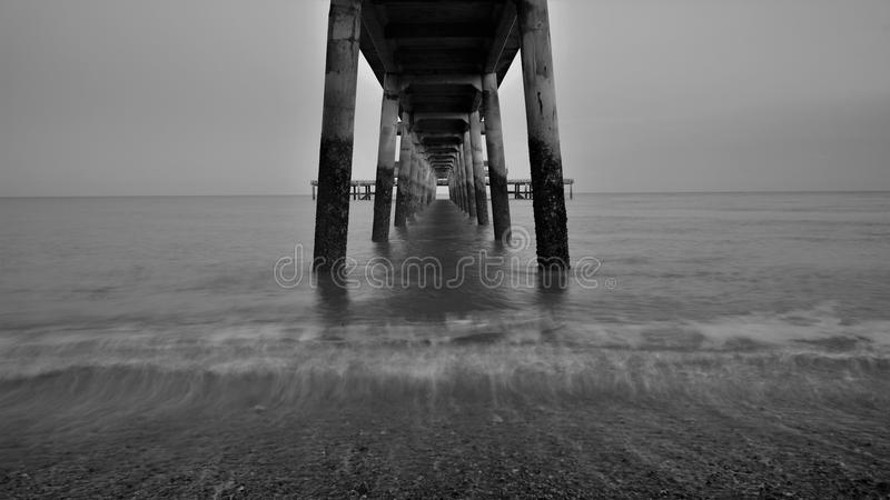 Under the pier at Deal, Kent in monochrome. stock photos
