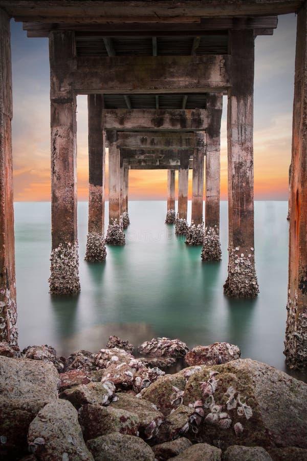 Under pylonerna av en lång bryggapirstrand arkivfoto
