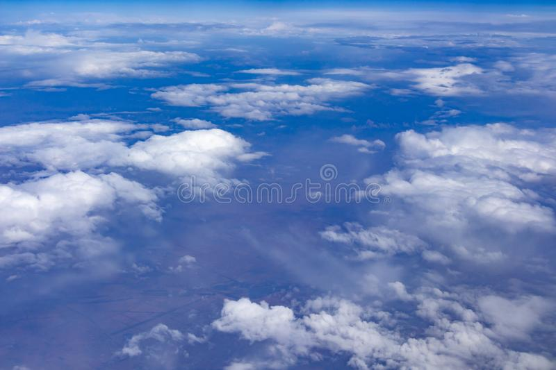 Under the sky, above the earth. Shoot the white clouds and the earth under the blue sky on the plane royalty free stock image