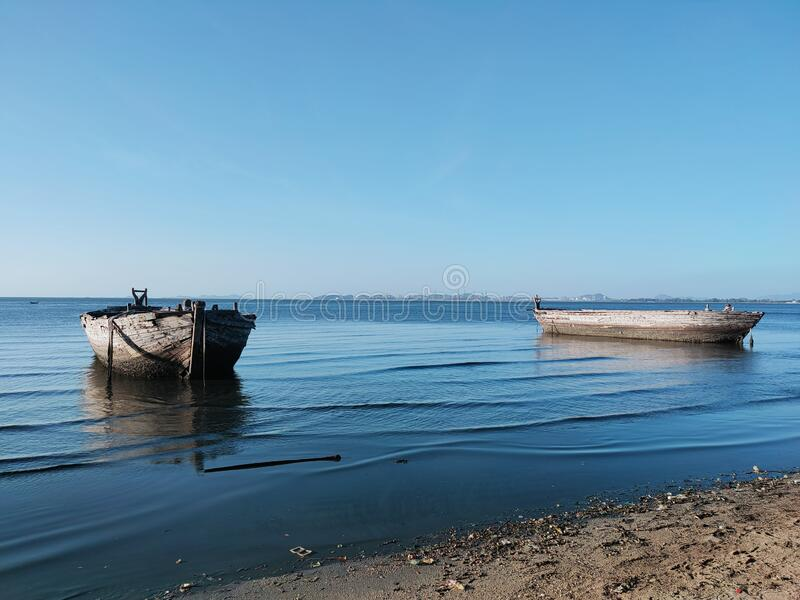 Under the sky and on the blue sea, there are old wooden boats. royalty free stock photo