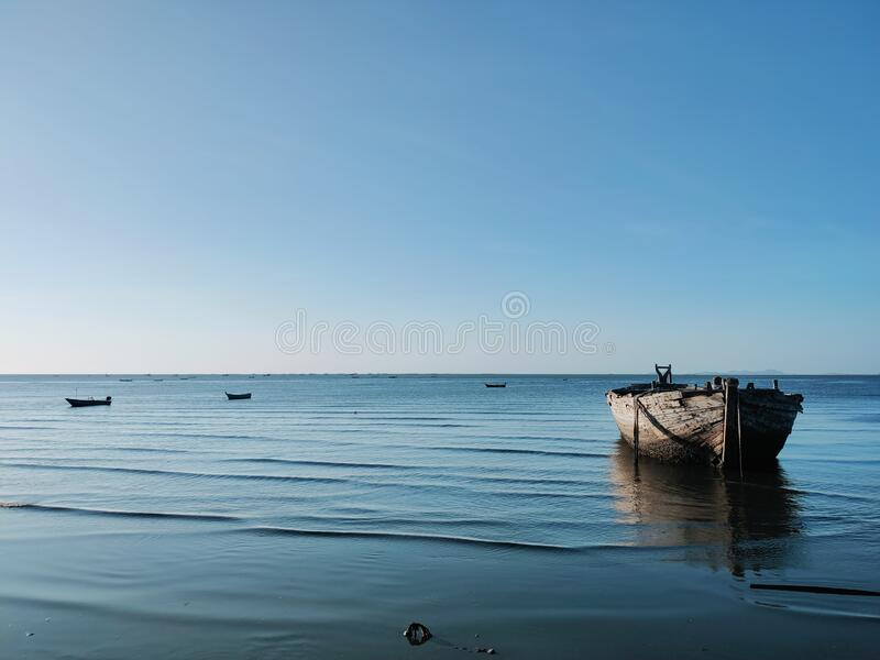 Under the sky and on the blue sea, there are old wooden boats. stock photo