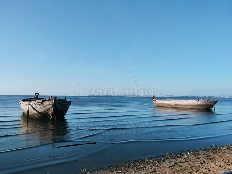 Under the sky and on the blue sea, there are old wooden boats. stock photos