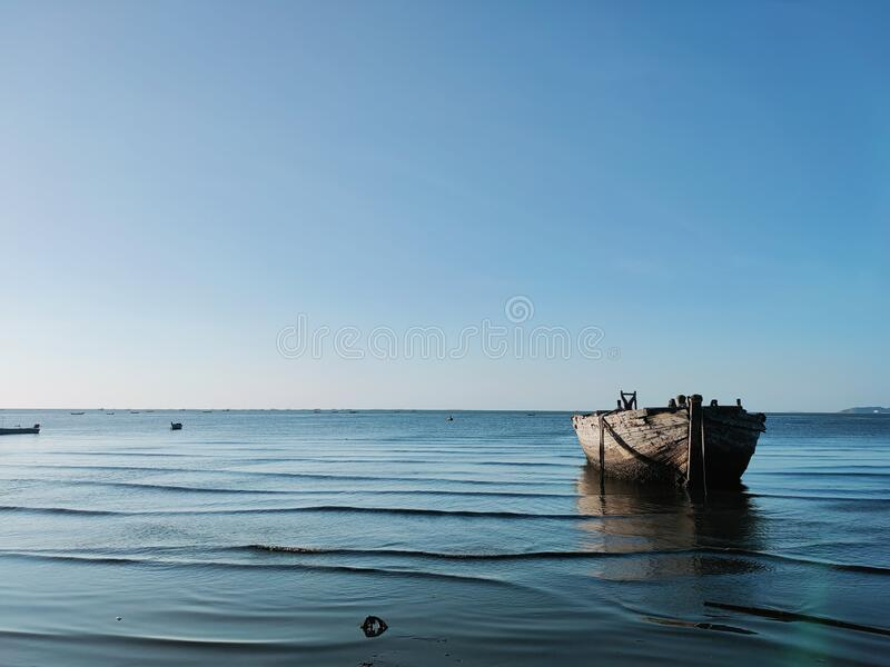 Under the sky and on the blue sea, there are old wooden boats. stock image