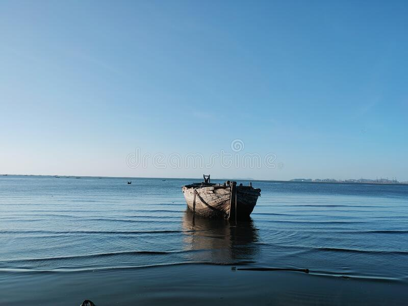 Under the sky and on the blue sea, there are old wooden boats. royalty free stock photography