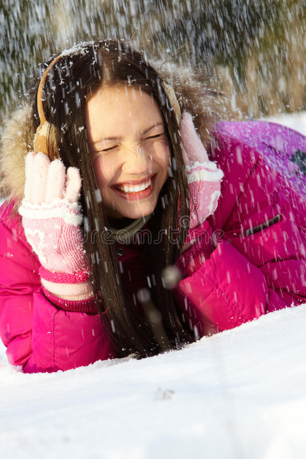 Under snowfall. Portrait of pretty girl lying on snow during snowfall royalty free stock images