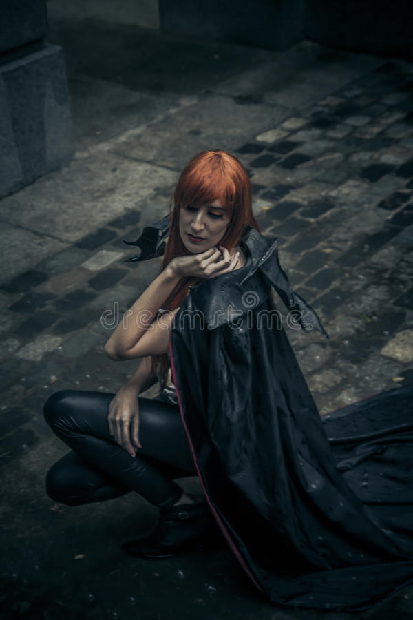 Under the storm, Beautiful vampire woman in palace gate, gothic. Fantasy huge coat stock photo