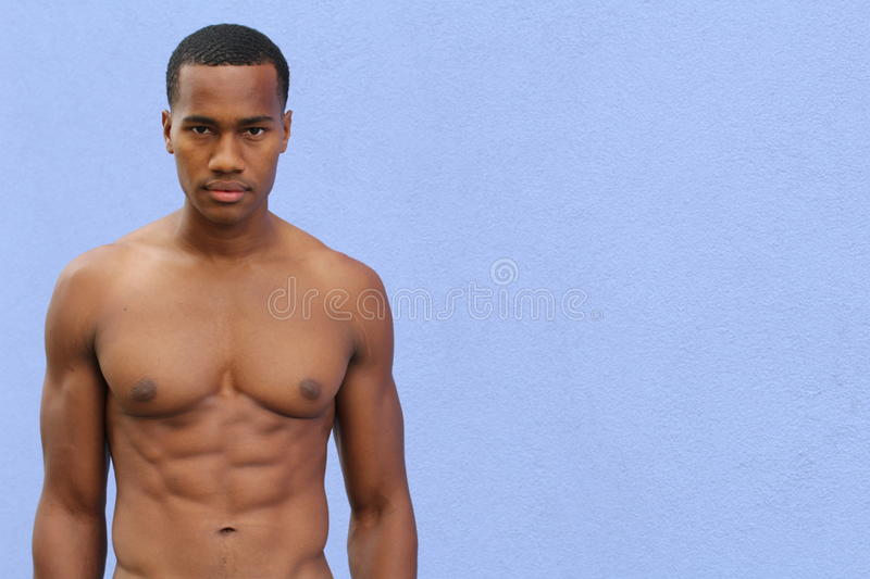 Under the sunshine, a masculine black guy, half naked, is standing by an alley with rough expression royalty free stock photo