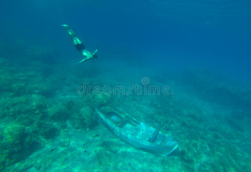 Under water young boy swims to the sunken boat royalty free stock photo