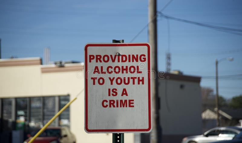 Underage Drinking Alcohol Crime Warning Sign. A local crime prevention and ordnance sign warns adults of legal drinking age that providing alcohol to youths and stock photo
