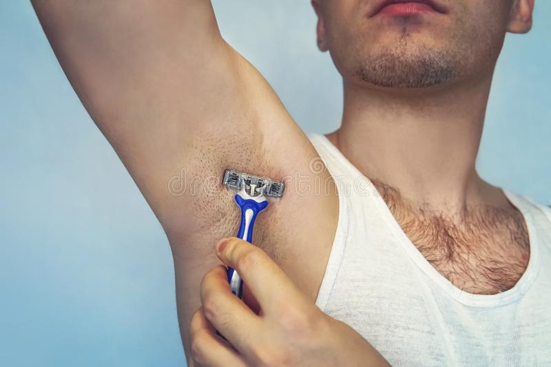 Underarm hair removal. Male depilation. Young attractive muscular man using razor to remove hair from his body. the self-care conc. Ept. epilation stock image