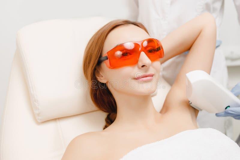 Underarm Laser-Haarabbaubehandlung Frauenfuß im Wasser stockbild