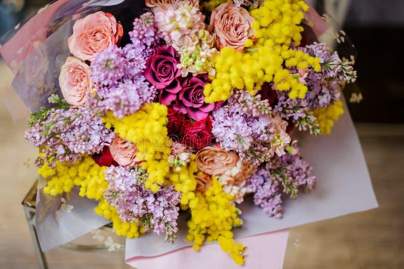 Underbar bukett av mång- den färgrosor, lilan och mimosan arkivfoton