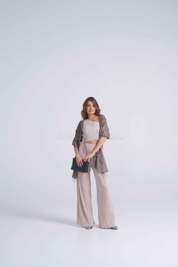 Underbar kvinna som poserar i stilfull kläder och tillbehör royaltyfria bilder
