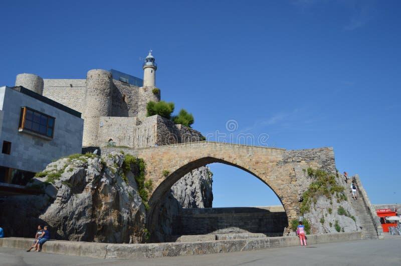 Underbar slottfyr Santa Ana And Roman Bridge Dated i det 12th århundradet på promenaden i Castrourdiales Augusti 27, arkivbild