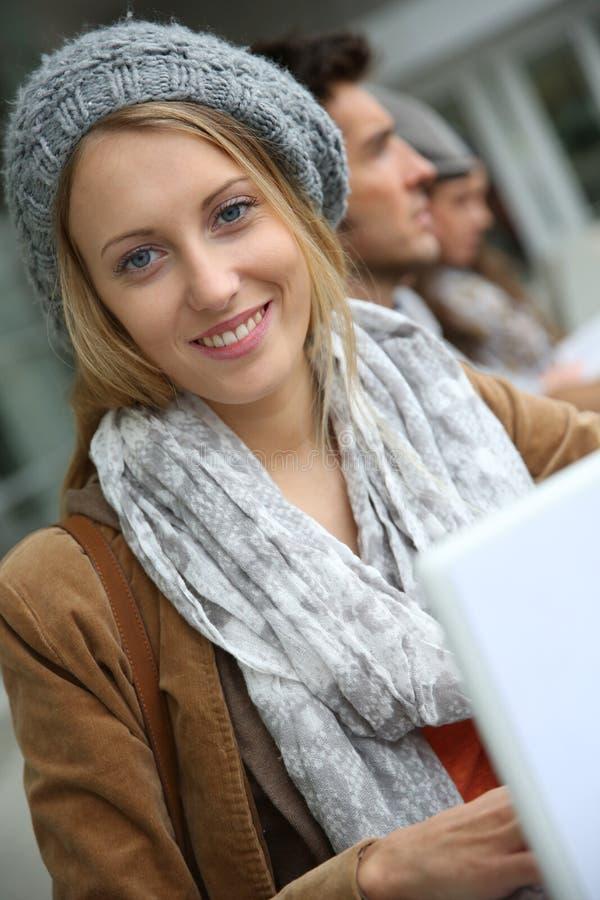Underbar studentflicka framme av universitetsområdet royaltyfri bild