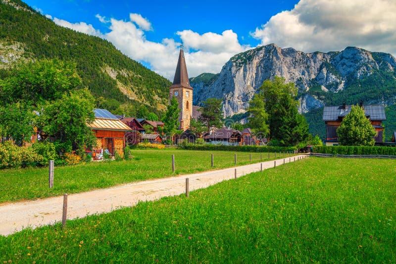 Underbara gröna fält och alpin by med kyrkan, Altaussee, Österrike royaltyfria foton